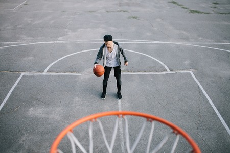 Teenager is standing on the playground and hitting the ball. He is getting ready for a throw. Boy want to reach the basket with the ball Фото со стока