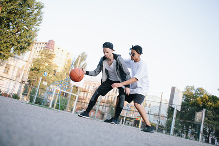 Serious fight in the middle of basketball game on the stadium. Two friends are playing against each other. Everybody wants to win