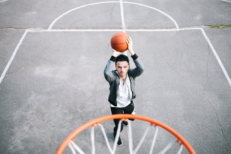 Guy is standing closer to the basket. He is throwing the ball into the basket. He has just started to do that. Boy hopes he will reach the basket Stock Photo