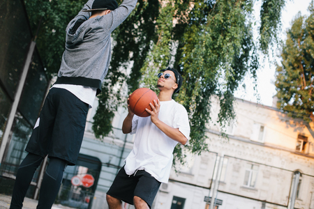 Two guys are training. The boy in white shirt is getting ready to throw the ball while the afroamerican guy is defencing the basket and trying to prevent ball hit the basket