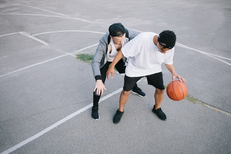 Two teenagers are playing basketball. The boy from the back is trying take back the ball while the afroamerican guy is playing with it Фото со стока