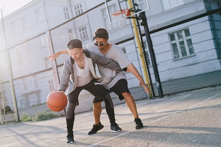 Caucasian guy and afro american young man are playing against each other on the playground. They are fighting for the possibility to get a ball. One of teenagers is leading the game Фото со стока