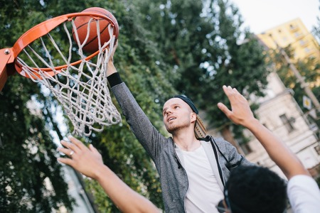 Two guys are playing basketball. One of them is almost thrown the ball into the basket. The other guy is trying to prevent his ooponent to get a point for a goal