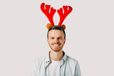 The pacified guy is looking at the camera. He is waiting for the new year. Young student with red horns, in a blue shirt before Christmas. It radiates positive emotions. Holiday vibes. Xmas mood