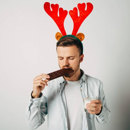 The guy eats chocolate with milk for breakfast. The male is filled with energy for the day with the help of a good snack. Sweet perfectly invigorates after the holidays. New Years junk food. Stock Photo