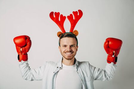 A guy in boxing gloves is waiting for hot packages. Man is determined to break prices. Knocks out discounts. Smiling before a cheap Christmas vacation on a last minute ticket. New Year offer. Stock Photo