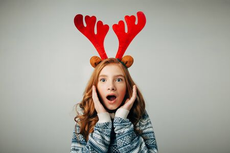 Girl with deer horns in a sweater smiles. She is shocked by the gift for the new year. Incredible discounts for Christmas and New Year. Isolated on white background. Stock Photo
