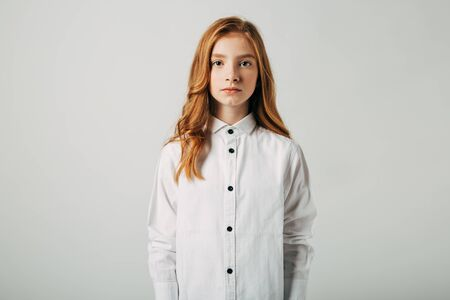 A young red-haired girl is looking at the camera. A girl with a worried video is trying to draw your attention to the problems of society. A student with red hair suffers from bullying and is depressed. Isolate on a white background.