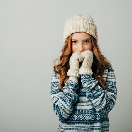 Teenager in a knitted hat, sweater and gloves. She is very warm and comfortable in this dress. The girl is very glad not to freeze this winter. Isolate on ber background Stock Photo