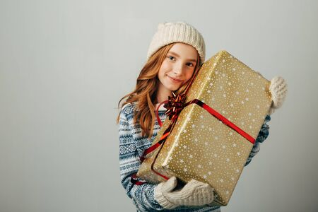 Teenager in a knitted hat, sweater and gloves. A girl hugs her Christmas present from her parents. Her friends pleasantly surprised the New Year. Isolate on white background
