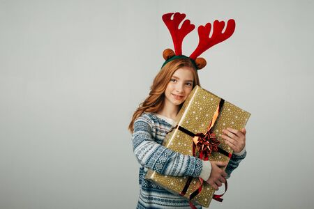 Red-haired girl hugs her present from parents at Christmas. The blue-eyed lady is happy about the New Year's gift from her best friends. The teenager is smiling. Isolated on a white background. Stock Photo