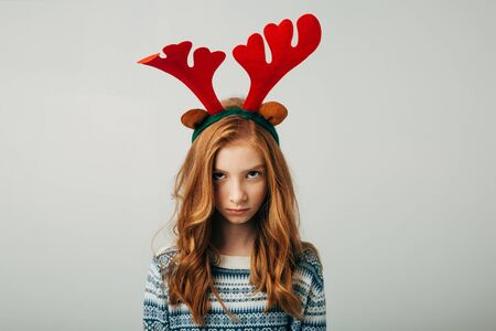 The red-haired girl was very offended by her parents on Christmas evening. Blue-eyed cutie angry at friends with a New Years gift. The teenager is depressed. Teenage mood is changing. Separately on a white background. Family problems