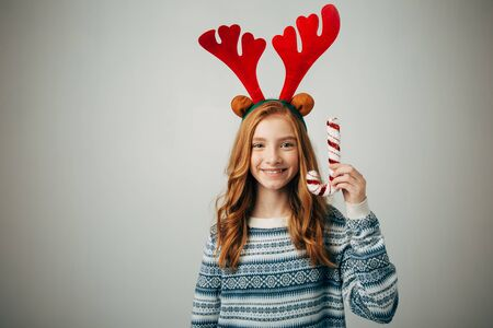 Girl in a sweater with red horns smiles, holding a Christmas lollipop in her hand. She will be happy to decorate the Christmas tree for the new year. Teenager with a sweetness. Isolated white background