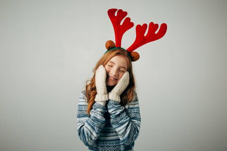 The girl in a sweater with red horns smiles, warming her face with gloves on her hands. Warm knitted gloves were very warm and comfortable. Isolated white background Stock Photo