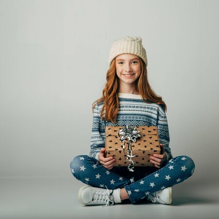 Teen in a knitted hat and sweater bought a Christmas present for parents at a low price. The girl is waiting when she can give a surprise to her friend for the new year. She smiling. Holiday discounts Isolate on a ber background.