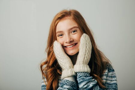The girl in a sweater smiles, warming her face with gloves on her hands. Warm knitted gloves were very warm and comfortable. Isolated white background