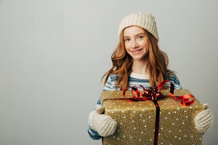 A teenager in a knitted hat, sweater and gloves is smiling. A girl hugs her Christmas present from her parents. Her friends pleasantly surprised the New Year. She was pleasantly surprised by the seasonal discounts. Isolate on white background