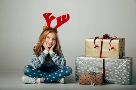 A teenager with red deer horns in a sweater bought Christmas gifts for parents at a low price. The girl is waiting when she can present surprises to her friends for the new year. She is smiling. Holiday discounts. Isolate on a ber background. Stock Photo