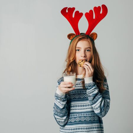 Red-haired girl with red horns in a sweater is very fond of milk with cookies a night. She did not wait for Santa and ate his treat. The teenager on Christmas before the new year. Isolate on white background