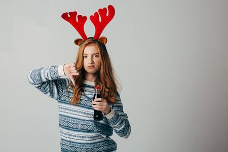 Red-haired girl refuses soda at Christmas so as not to harm sugar with her health. teenager with red deer horns before the new year. She does not approve of sahara drinks. Isolate on white background