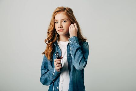 Red-haired girl listens to music in small headphones. She does not want to talk to her parents and turns on something on her smartphone. Teenager is a bullying victim and seeks rest in creativity. Isolated Stock Photo