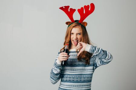Red-haired girl refuses soda at Christmas so as not to harm sugar with her health. teenager with red deer horns before the new year. She does not approve of sahara drinks. Builds a grimace of disgust. Isolate on white background