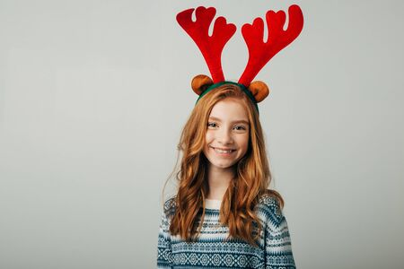 A young red-haired girl smiles and looks at the camera. The student with red hair is very glad to see you. She is preparing for the celebration of the new year. A schoolgirl with freckles in a blue sweater surprises with happiness for Christmas. Isolate on a white background.