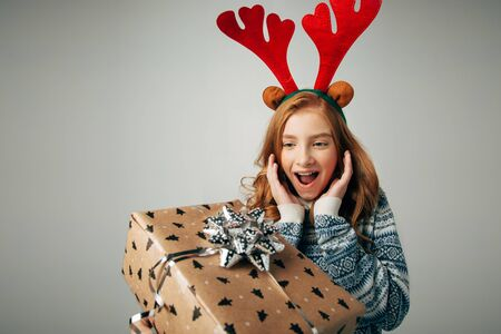 Girl with deer horns in a sweater smiles. She is shocked by such a great New Year gift. Parents pleasantly surprised the teenager with a surprise at Christmas from her friends. Isolated on white background