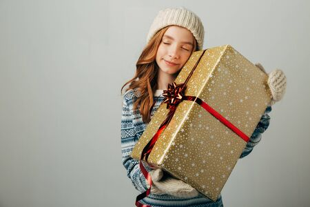 The teenager in a knitted hat, sweater and gloves closed her eyes in pleasure. A girl hugs her Christmas present from her parents. Her friends pleasantly surprised the New Year. Isolate on white background