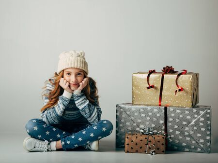 A teenager in a knitted hat and sweater bought Christmas gifts for parents at a low price. The girl is waiting when she can present surprises to her friends for the new year. She is smiling. Holiday discounts. Isolate on a ber background. Stock Photo