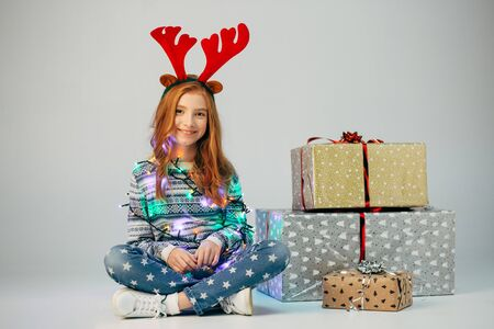 A teenager with red deer horns in a sweater bought Christmas gifts for parents at a low price. The girl is waiting when she can present surprises to her friends for the new year. She is smiling. Holiday discounts. She wrapped herself in a garland to create a good mood. Isolate on a ber background. Stock Photo