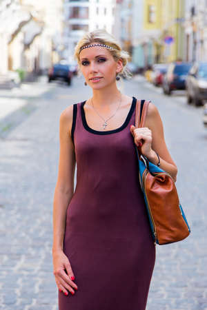 blondy: Young girl walking down the street in a dress holding a bag in his hand Stock Photo