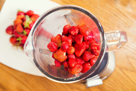 strawberries in a blender. the background white dish and table