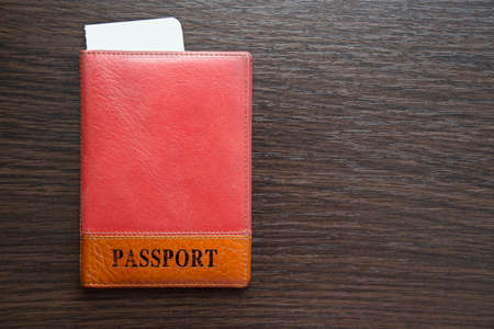 ides: passport and airline tickets in orange leather cover on a table