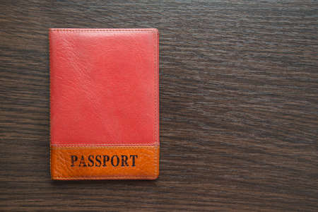 ides: passport  in orange leather cover on a table