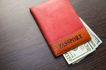 ides: Passport with money lying on a wooden table
