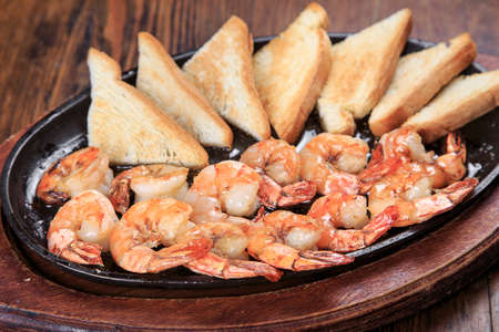 tiger shrimp: On the table is a pan with prawns grill and toast, close-up Stock Photo