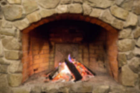 stone fireplace: in the wood burning stone fireplace. blurred background