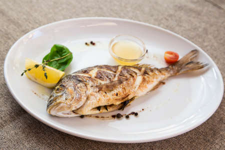 dorade: dorado grilled on a plate served with a slice of lemon and sauce