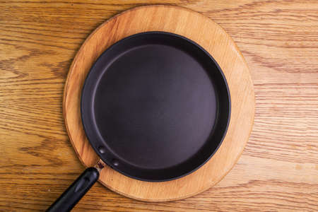panful: empty pancake pan on a wooden board, view from above