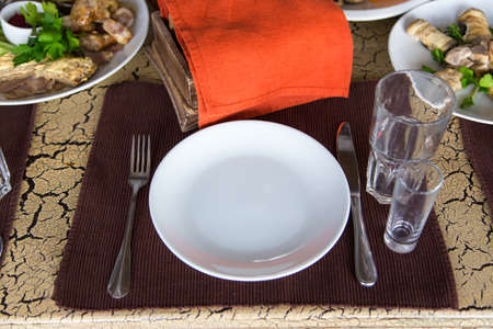 fork glasses: on the brown napkin, on the table is flatware per person, fork, knife, two glasses, on the background there are rolls of eggplant and grilled vegetables