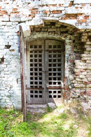 rejas de hierro: celos�a puerta de la vendimia en la pared del castillo en ruinas