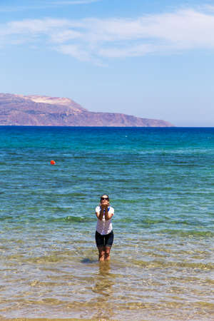 healthy girls: dressed girl is standing knee-deep in the sea, and sends an air kiss