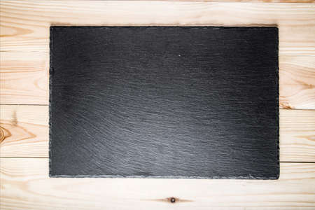 black slate board for serving on a light wood surface, top view