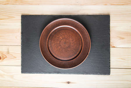 red clay: plate of red clay on the slate board. slate board on a wooden surface, top view