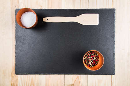 peppar: multicolored peppers peas and salt in a clay cup on a slate board, wooden kitchen spatula, top view