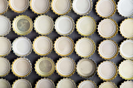 twist cap: upturned caps of beer lined up in rows, top view