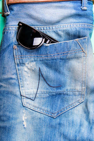 neatly stacked: sunglasses in the pocket of jeans, jeans neatly stacked on wooden background, top view