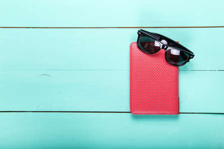 ebook cover: e-book in a red cover and sunglasses, a modern gadget, top view