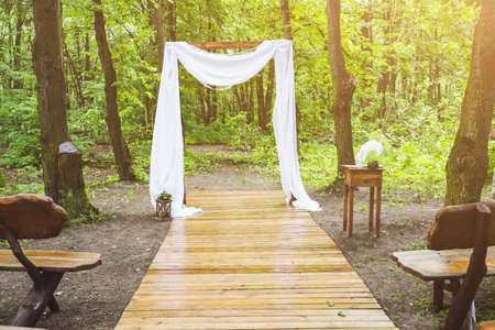arch for the wedding ceremony, decorated with cloth , is in a pine forest Banco de Imagens